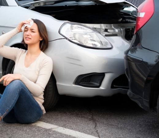 car accident victim sitting next to her car